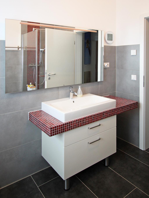 Waschbecken mit Unterschrank und durchgehender gefliester Arbeitsplatte