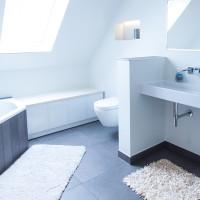 Badezimmer-Einbauschrank mit weißen Glastüren und weiß geölter Holzplatte.