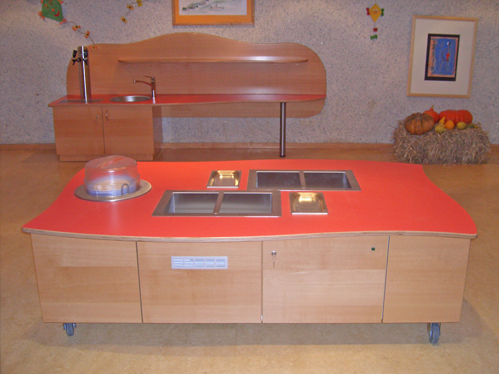 Ein rollbarer Buffetresen und eine Bueffetzeile mit Wasserspender und Spüle für Kinder