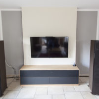 HIFI-Möbel in Buche und Möbellinoleum. Klappe mit Lochblech. Der TV ist an der Rückwand aufgehängt, die Kabelführung ist nicht sichtbar.