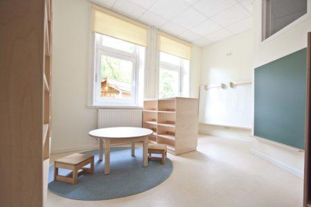 Kinderatelier mit Malwand, Tisch und Regalen