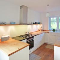 Küche mit massiver Eichenarbeitsplatte und Regal, Unterschrank mit weißlackierten Rahmen-Füllung Fronten. Eine Natursteinplatte um das Kochfeld