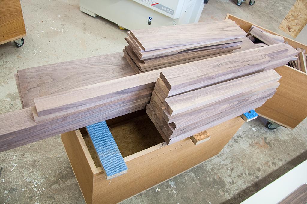 Aus der Nussbaumbohle zugesägte und abgerichtete Einzelteile für einen Kleiderschrank