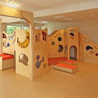 Spielpodest mit Rollwagen, Wellentreppe und bunten Plexiglasfenstern