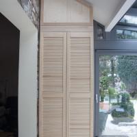 An eine Dachschräge angepasster Schrank mitLamellentüren